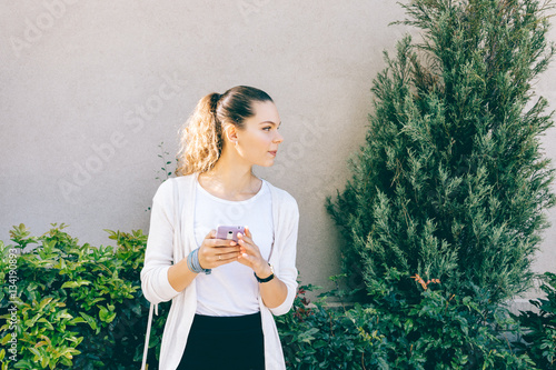 Fotografía  Attractive girl in white cardigan using a mobile phone outdoors