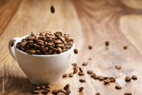Photo  cappuccino cup with roasted coffee beans on wood table, with copy space
