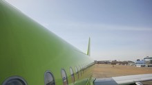 Airplane Stays In Airport Between Flights And Wait Passengers. We Are Above Aircraft Wing. First We Can See Green Body With Lot Of Windows, Tail Of Plane And White Wing At End. On Background There Is