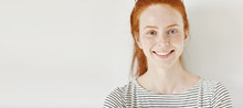 Heterochromia Concept. Attractive Young Woman With Ginger Hair And Different Colored Eyes Smiling Happily, Posing Isolated Against White Studio Wall With Copy Space For Your Informational Content