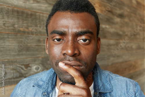 Handsome young dark-skinned employee with stubble holding index finger on his li Canvas Print