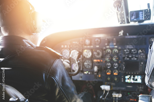 Adult airplane pilot wearing headset and outfit performing his job, sitting inside aircraft cockpit at steering control with modern dashboard Tablou Canvas