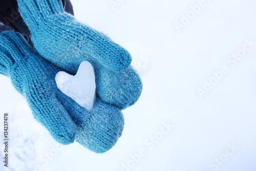 Fotografija  Mittens holding a snow heart shape