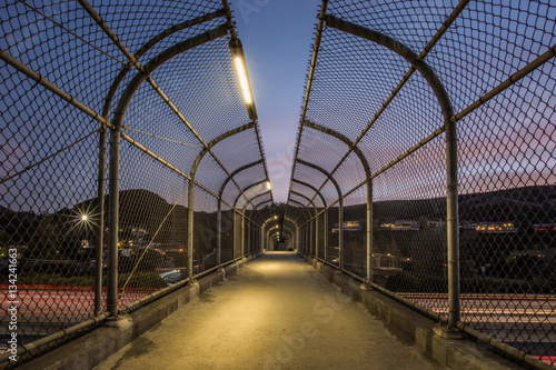 Pedestrian Footbridge with Long Exposure of US 101 Traffic Lights During Sunset Poster