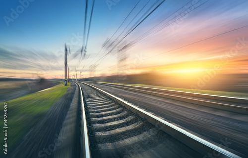 Tuinposter Spoorlijn Railroad in motion at sunset. Railway station with motion blur effect against colorful sky, Industrial concept background. Railroad travel, railway tourism. Blurred railway. Transportation. Vintage