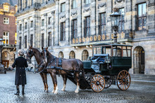 AMSTERDAM, NETHERLANDS - DECEMBER 17, 2017: Carriage With Horses On The Central Square Of Amsterdam. On December 17, 2016 In Amsterdam - Netherlands.