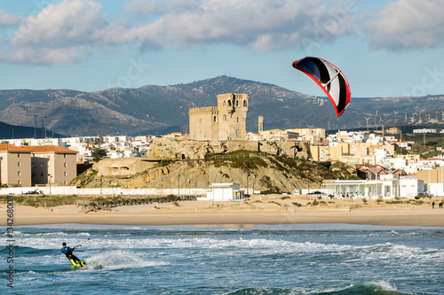 Man practicing kitesurfing on the beach of Tarifa, Spain. Tarifa is considered the capital of the wind, and favorite place for lovers of this sport.