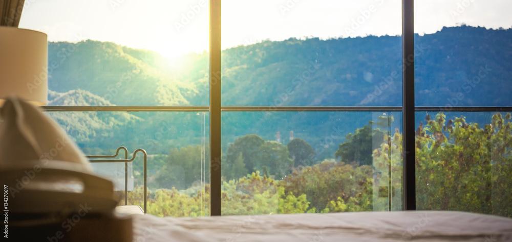 patrząc przez duże okno w piękne mgliste wzgórza z kolorowy zachód słońca. <span>plik: #134278697 | autor: escapejaja</span>