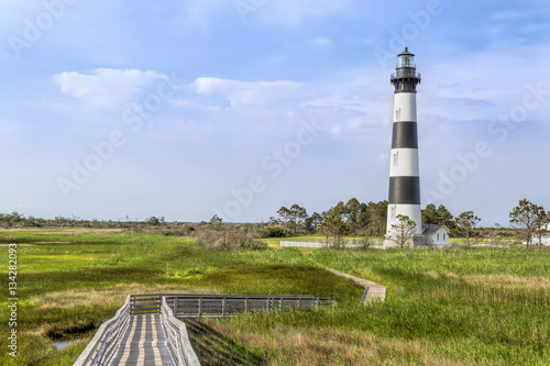 Foto op Plexiglas Vuurtoren A board walk leads the eye to the historic Bodie Island Lighthouse at Cape Hatteras National Seashore on the Outer Banks of North Carolina.