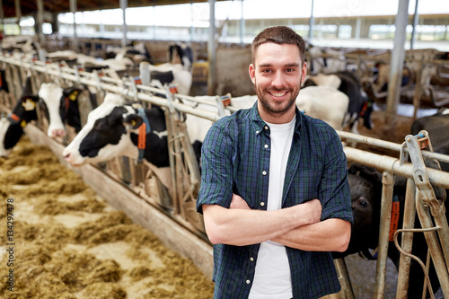 Fotografía  man or farmer with cows in cowshed on dairy farm