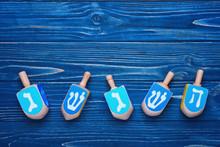 Dreidels For Hanukkah On Blue Wooden Table
