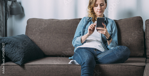 Fotografie, Obraz  Front view of young woman in denim shirt sitting at home on couch and using smartphone