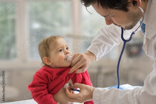 Fotografia  Pediatrician doctor is examining child with stethoscope.