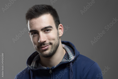 Fotografie, Obraz  Charming young unshaven man smiling at camera with head slanted.
