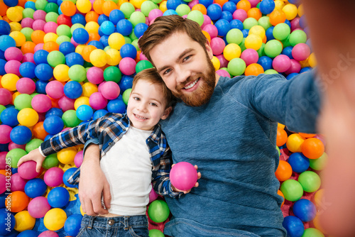 Son with dad taking selfie in colorful balls pool