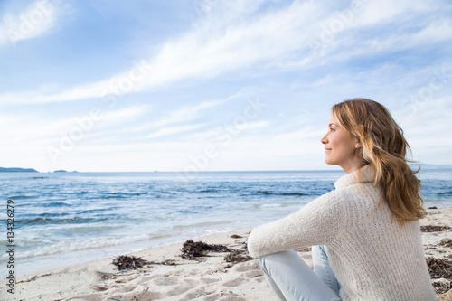 Photo  femme en hiver assise au bord de la mer