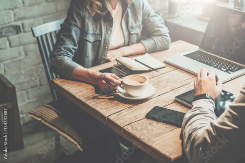 Businessman And Businesswoman Sitting At Table In Coffee Shop And Discuss  Business Plan.