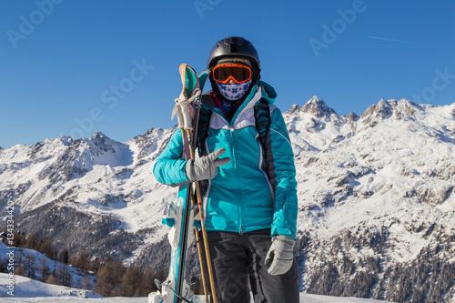 Fototapeta Ski, skier, sun and winter fun - woman enjoying ski vacation. Sport, leisure and people concept - happy young woman in ski goggles outdoors. Ski resort obraz na płótnie