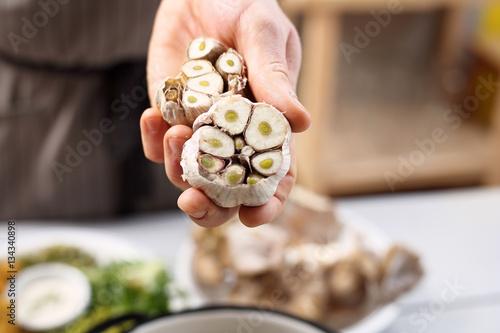 Fototapeta czosnek w kuchni. Kucharz trzyma główkę świeżego czosnku.  obraz