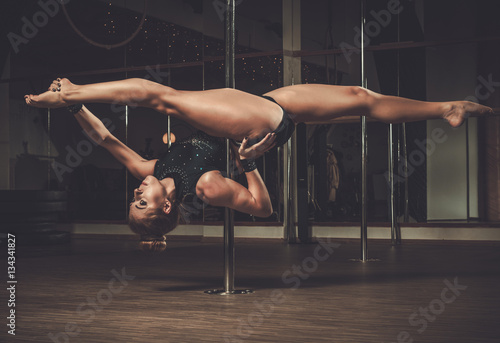 Valokuva Sexy young woman performing pole dance on pole