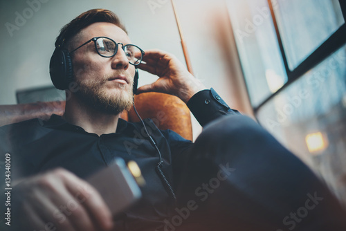 Photo  Portrait handsome bearded man wearing glasses,headphones listening to music at modern home