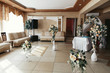 Cosy hall of retaurant decorated with white and beige flowers fo