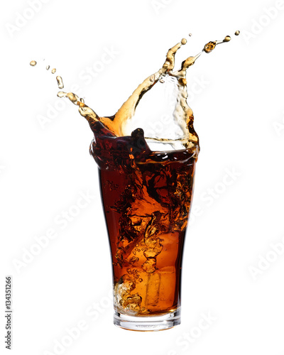Foto Cola splashing out of a glass., Isolated white background.