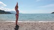 Pretty Caucasian girl shows gymnastic exercises cartwheel on a sandy beach near the sea