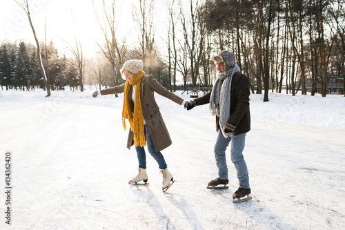 Senior couple in sunny winter nature ice skating. Wallpaper Mural