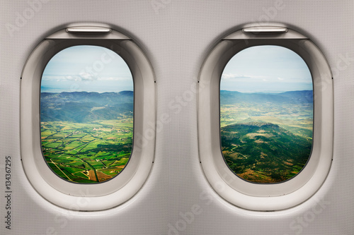 Tuinposter Vliegtuig Sardinia countryside with the sea in the distance viewed from inside an airplane windows climbing after take off