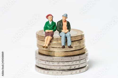 Fotografía  Rentner / älteres Ehepaar sitzt auf Euromünzen