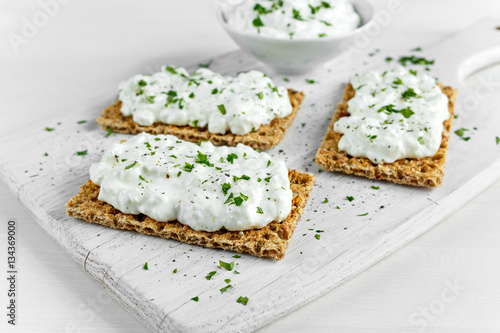 Fotografía  Homemade Crispbread toast with Cottage Cheese and parsley on white wooden board