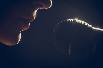 Fototapeta Woman singing to microphone
