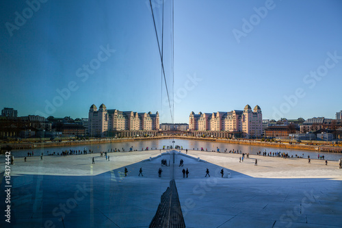 View on a side of the National Oslo Opera House with city reflected in glass Poster