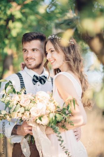 bride and groom hugging at the wedding in nature. Fototapeta
