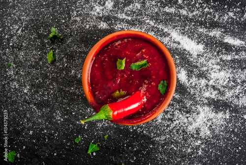 Tuinposter Hot chili peppers Hot Tabasco sauce in a bowl, top view. With ingredients - a slice of hot pepper and salt, copy space