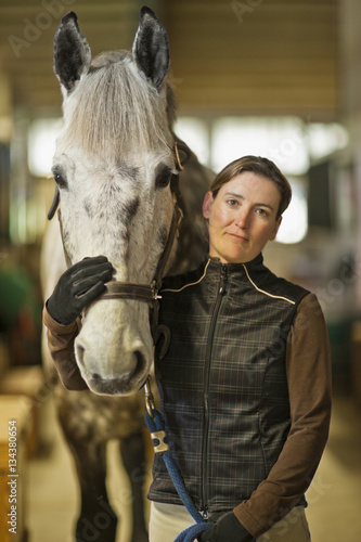 Portrait of a mid adult woman and her horse in a stable.