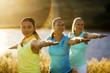 Three women practicing yoga in a rural field.