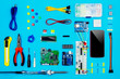 Top view of desktop of hardware engineer on blue background. Smartphone with connectors, microcontroller, hdd and hardware equipment