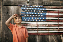 Boy Saluting In Front Of An American Flag