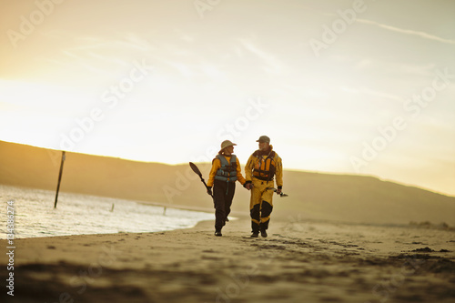 Happy senior couple walking hand in hand while carrying paddles along a sandy beach.