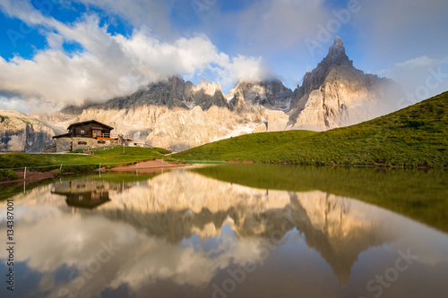 Poster Reflexion The Pale di San Martino peaks (Italian Dolomites) reflected in the water, with an alpine chalet on background.