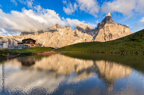 Foto auf Gartenposter Reflexion The Pale di San Martino peaks (Italian Dolomites) reflected in the water, with an alpine chalet on background.