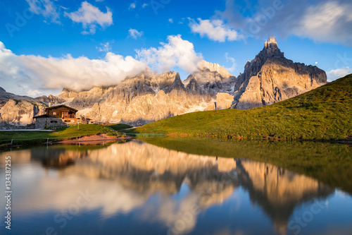 Foto auf Gartenposter Reflexion The Pale di San Martino peaks (Italian Dolomites) reflected in the water at sunset, with an alpine chalet on background.