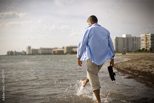 Mature adult man walking through the sea on a beach.