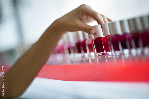 Hand on a mid adult woman choosing a nail polish color at a beauty salon Poster