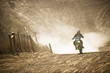 Motorbike racer racing through a dirt road