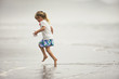Happy young girl playing in shallow water on a beach.