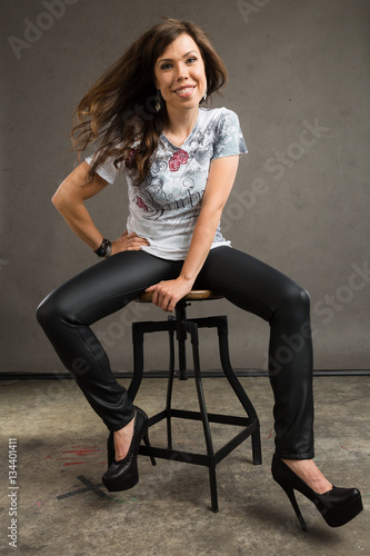 7d6b866a3d2 Young caucasian woman with brown hair, a grey top, leather pants ...