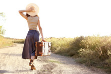 Young Woman With Suitcase Walk...